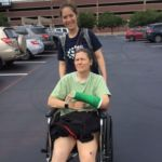 my daughter pushing me across campus in my wheelchair